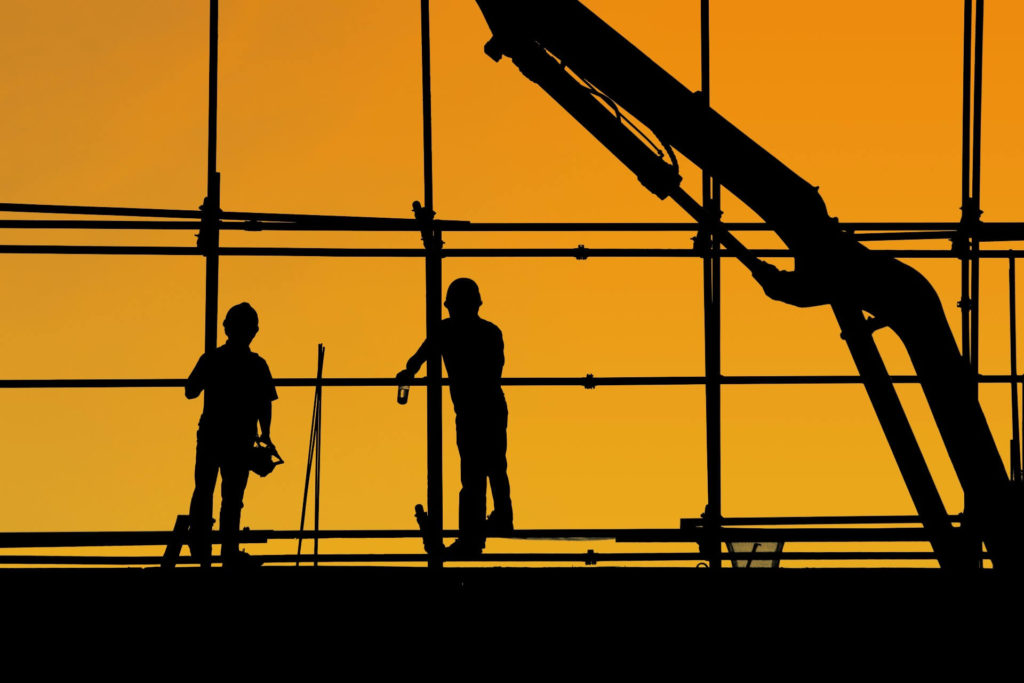 Two workers on a construction site with an orange background